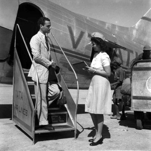 An air hostess of an airline sees to a passenger.